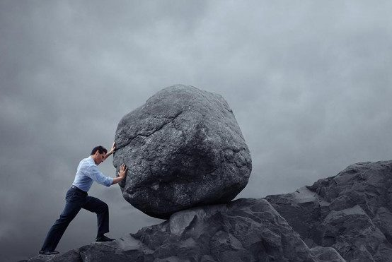 Man pushing huge rock uphill